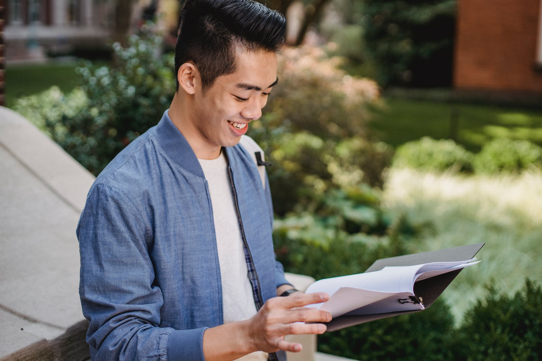 smiling ethnic student reading document in park